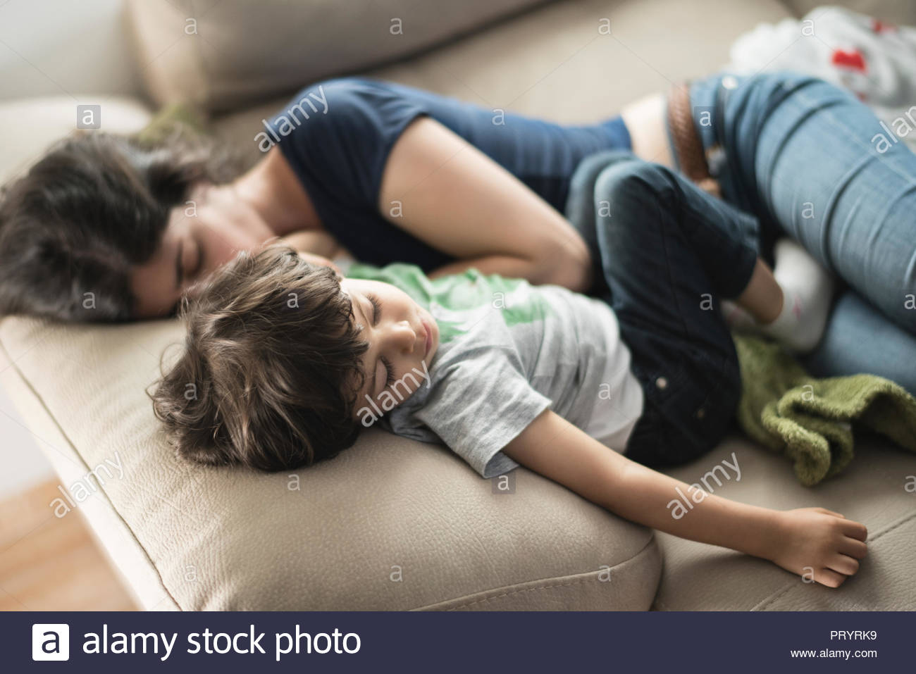 Mother and son taking a nap on couch - Stock Image