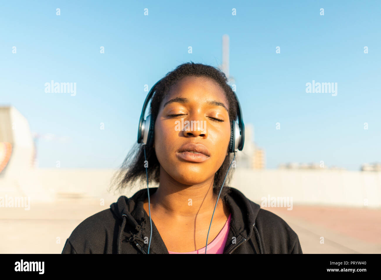 Young sportive woman listening music with headphones, eyes closed - Stock Image