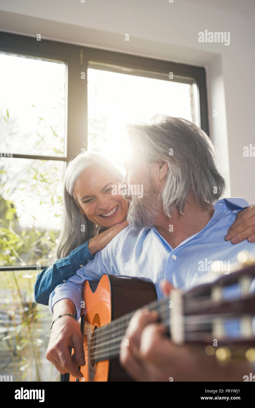 Senior playing guitar and singing loud for his wife - Stock Image