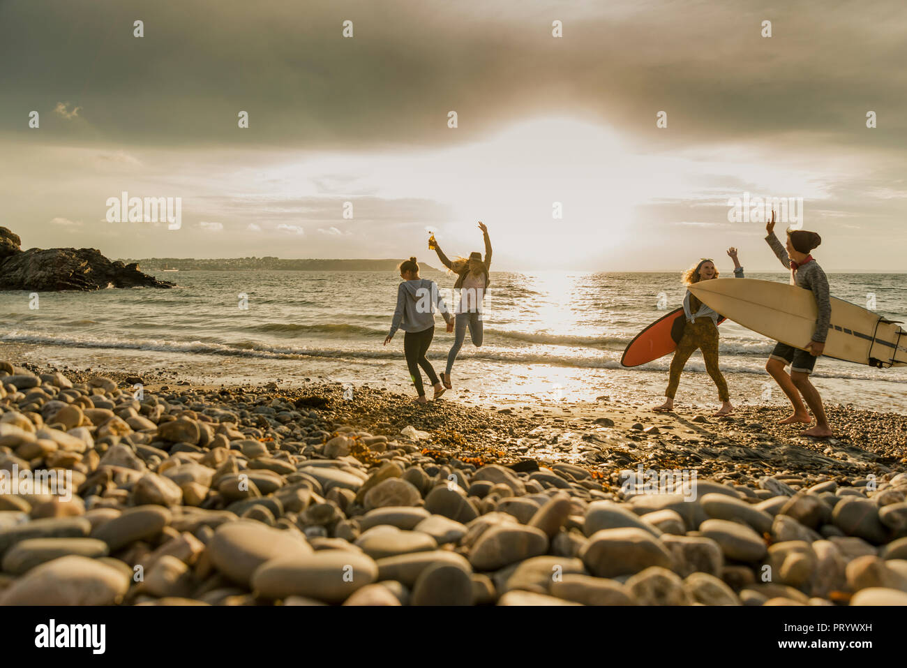 Excited friends with surfboards on stony beach - Stock Image