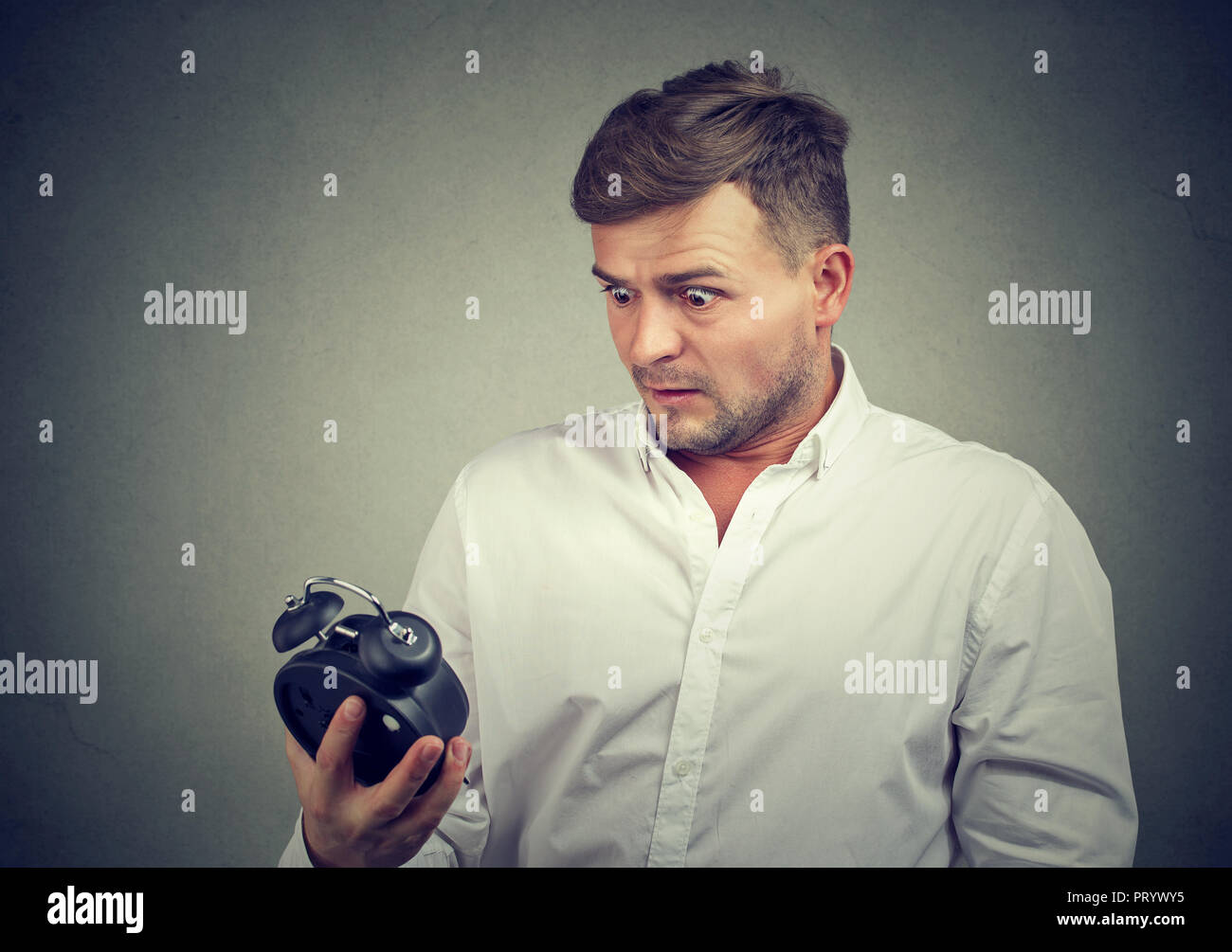 Young man in formal shirt looking at alarm clock with fear being late on gray background - Stock Image