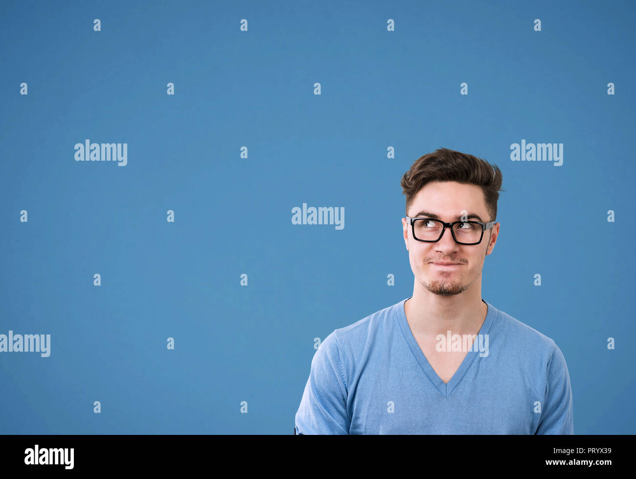 Young casual man in glasses looking up wonder making plan on bright blue background - Stock Image