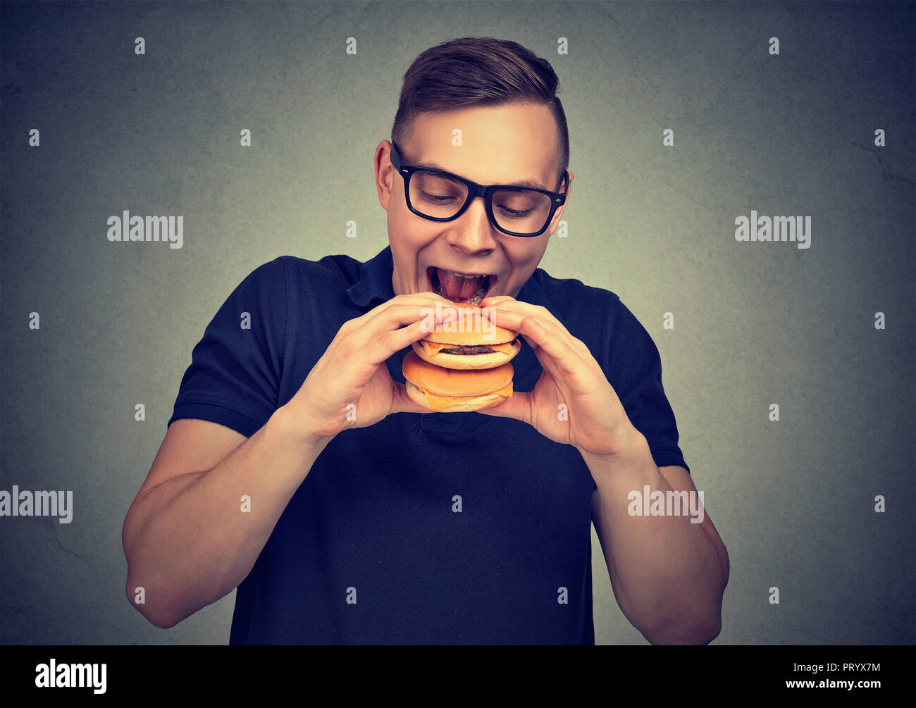 Casual man in glasses excited with double cheeseburger while starving and craving for fast food - Stock Image