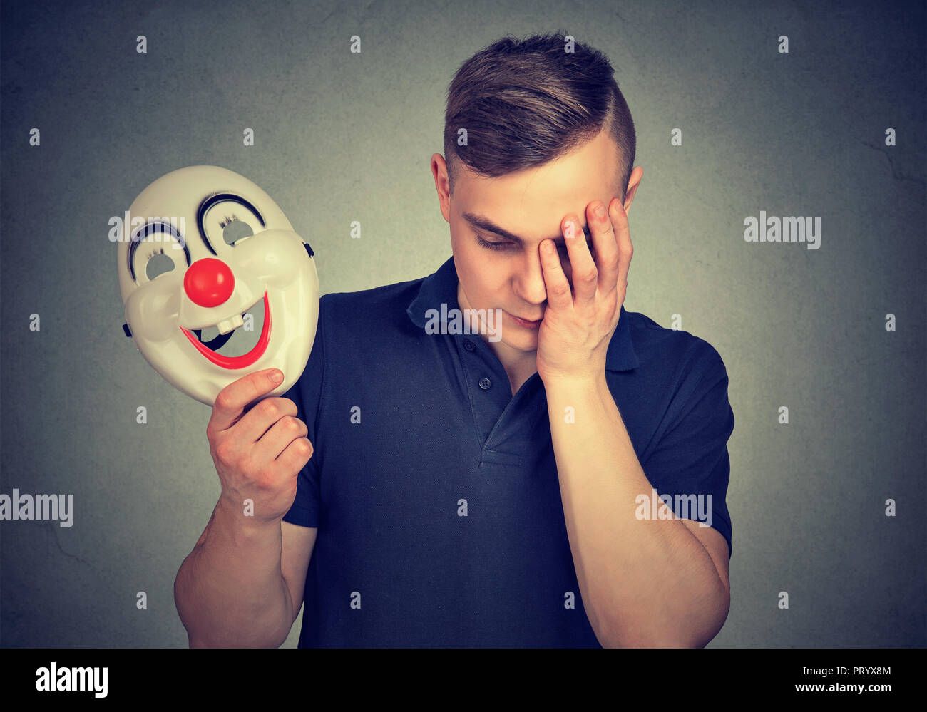 Young man holding colorful clown mask and looking upset being in depression and hiding feelings - Stock Image