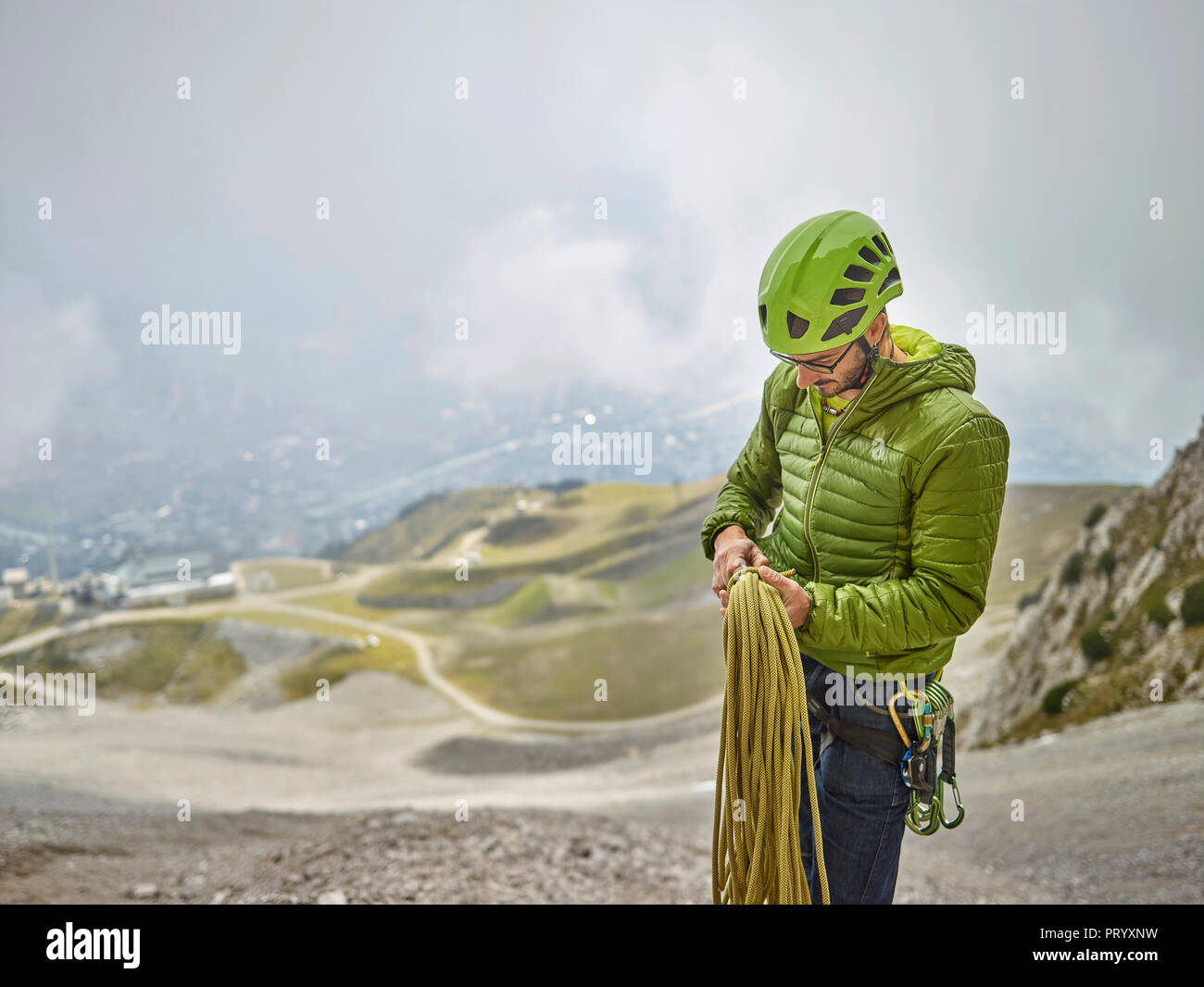 Austria, Innsbruck, Nordkette, man with rope and climbing equipment - Stock Image
