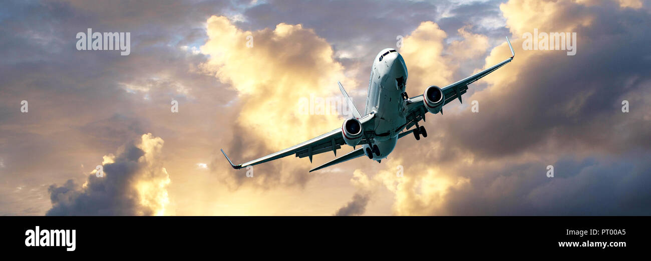 A passenger jet airliner flying overhead closeup with a golden yellow coloured cumulus cloud formation in a grey-blue sky. Atmospheric beauty. - Stock Image
