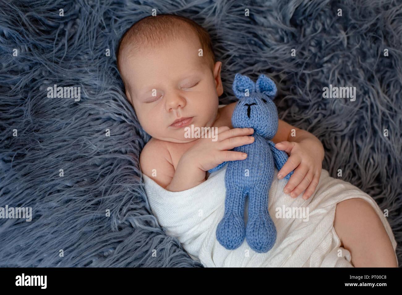 Newborn baby boy in bed. New born child sleeping under a white knitted blanket. Children sleep. - Stock Image
