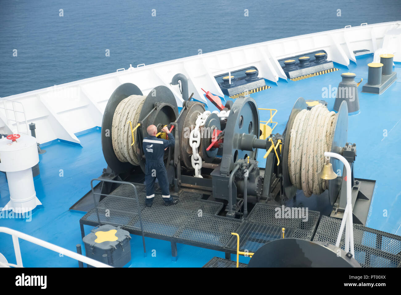 Aegean Sea, Greece/ July 17, 2018: Seaman working on foredeck of ferry boat - Stock Image