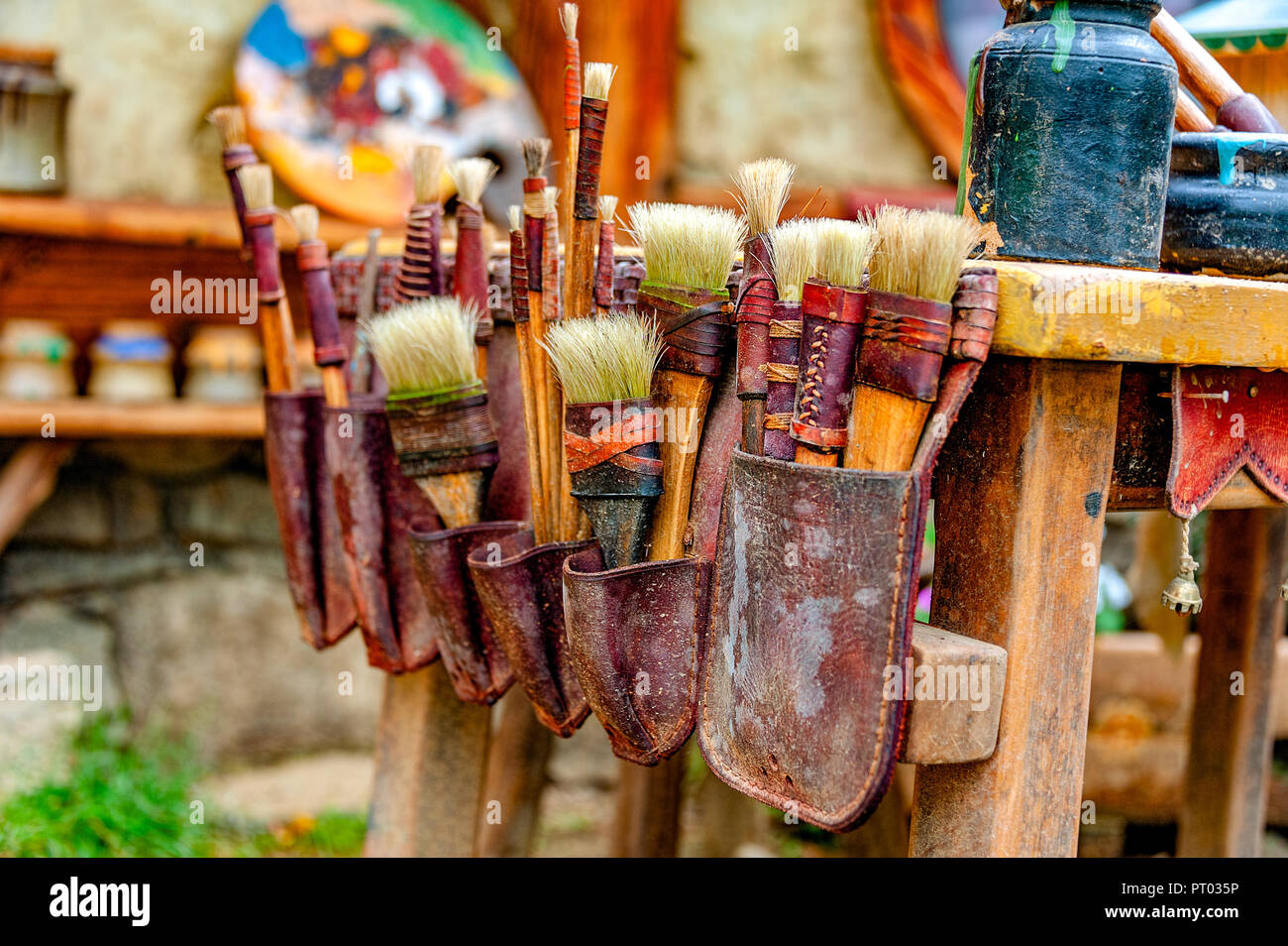 ARTIST's POUCH OF PAINT BRUSHES. Rustic painter's brushes of various shapes and sizes in an old leather pouch attached to one side of a table. - Stock Image
