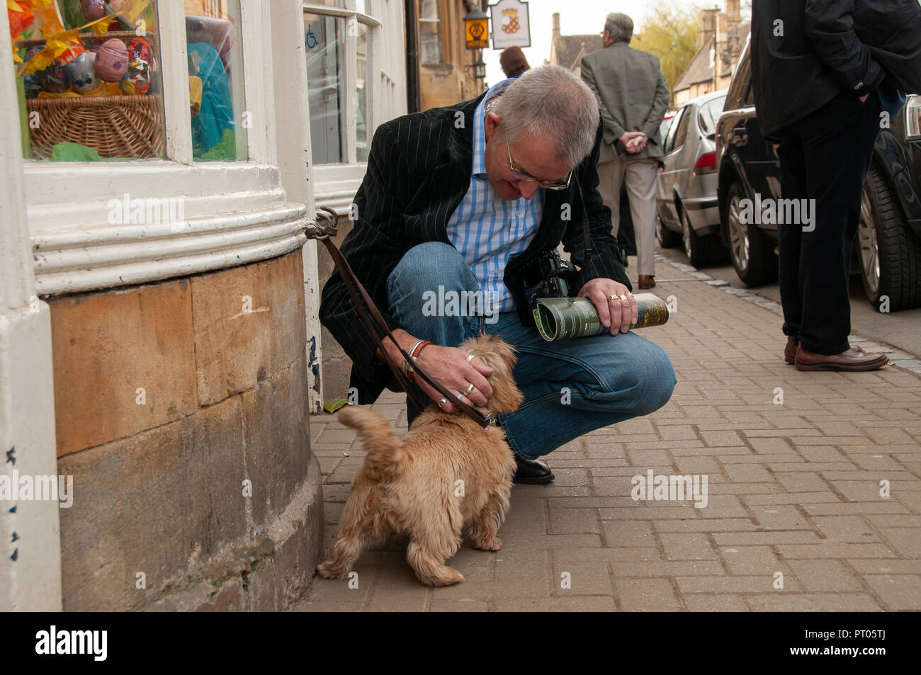 Older smartly dressed man in shirt and blazer, holding a rolled up magazine squatting down to stroke a little terrier tied up on the pavement outside. - Stock Image