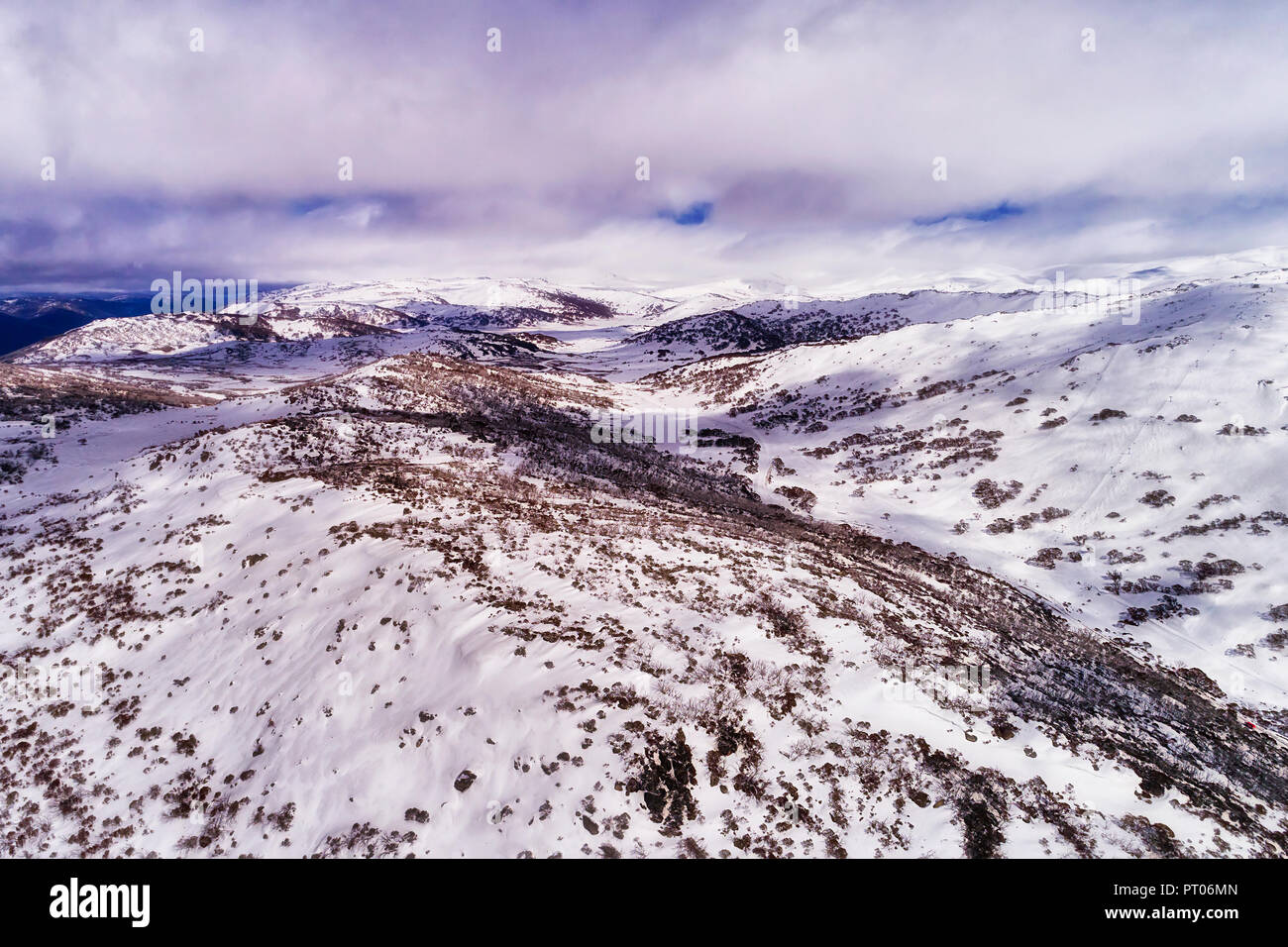 WHite snow slopes of the highest mountains in Australia under white clouds along Perisher valley with thick snow and ski resort sports tracks. - Stock Image