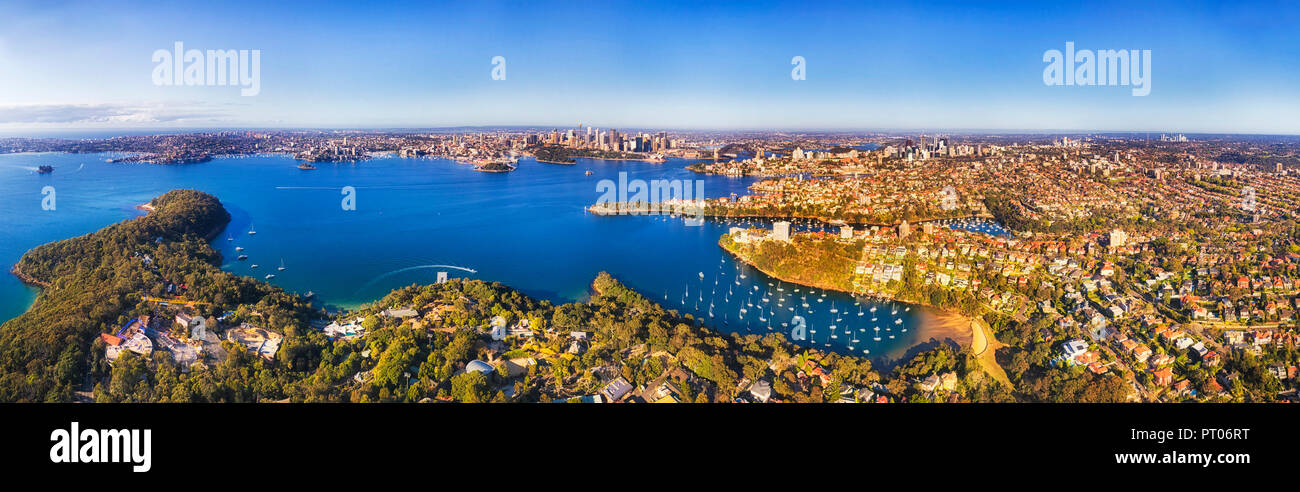 Clear blue waters of Sydney harbour between shores on bright sunny day in aerial view of city CBD landmarks from wealthy lower north shore suburbs of  - Stock Image