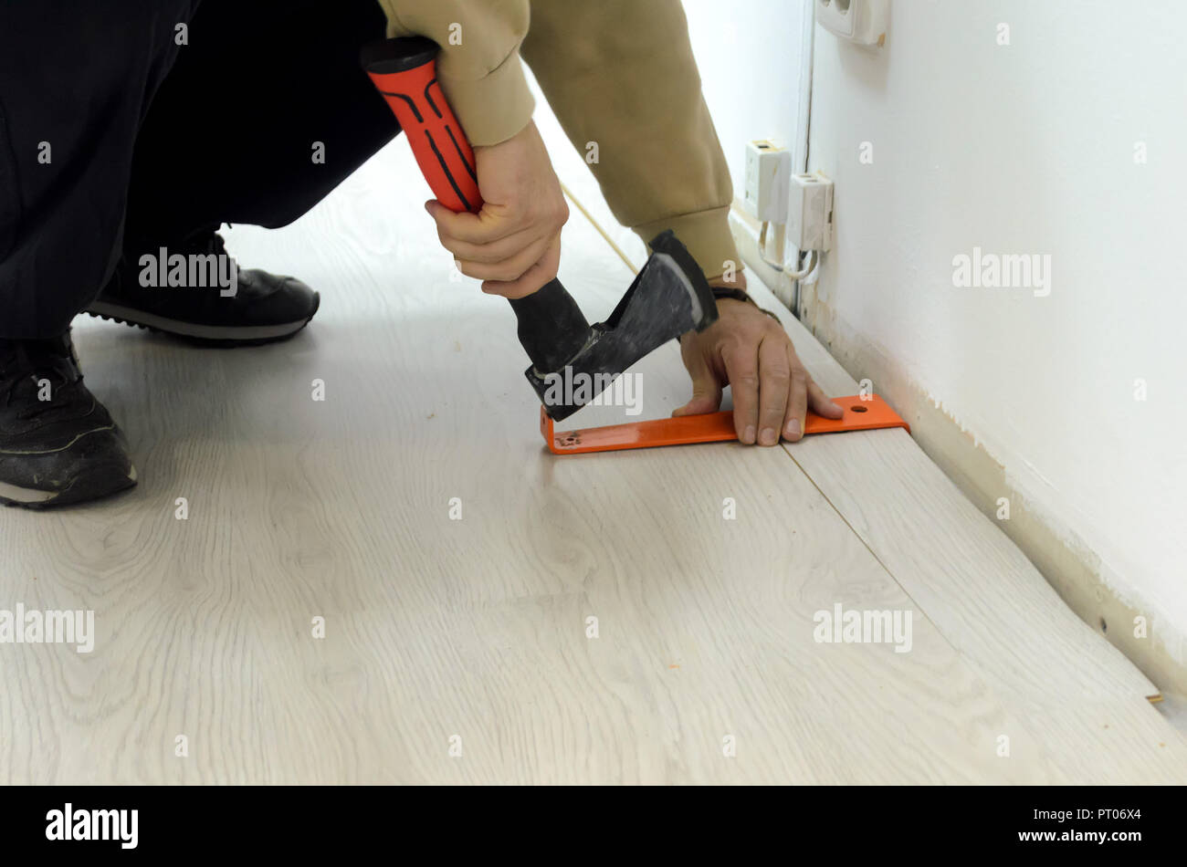 Renovation of an apartment, man laying laminate flooring in the room. - Stock Image