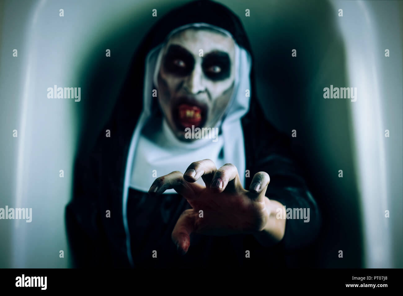 closeup of a frightening evil nun, wearing a typical black and white habit, with a threatening gesture, emerging from a white coffin - Stock Image