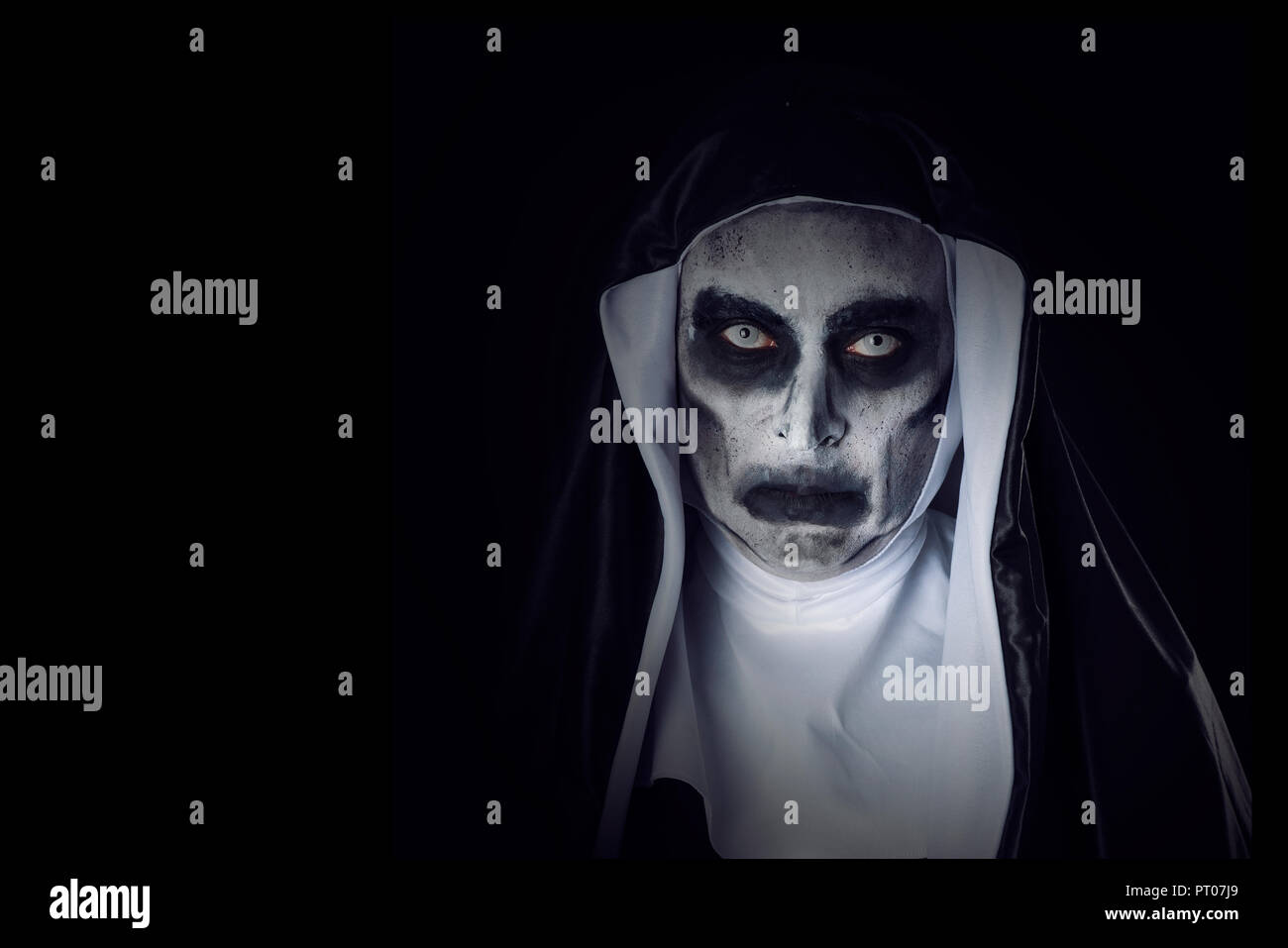 portrait of a frightening evil nun, wearing a typical black and white habit, against a black background, with some blank space on the left - Stock Image