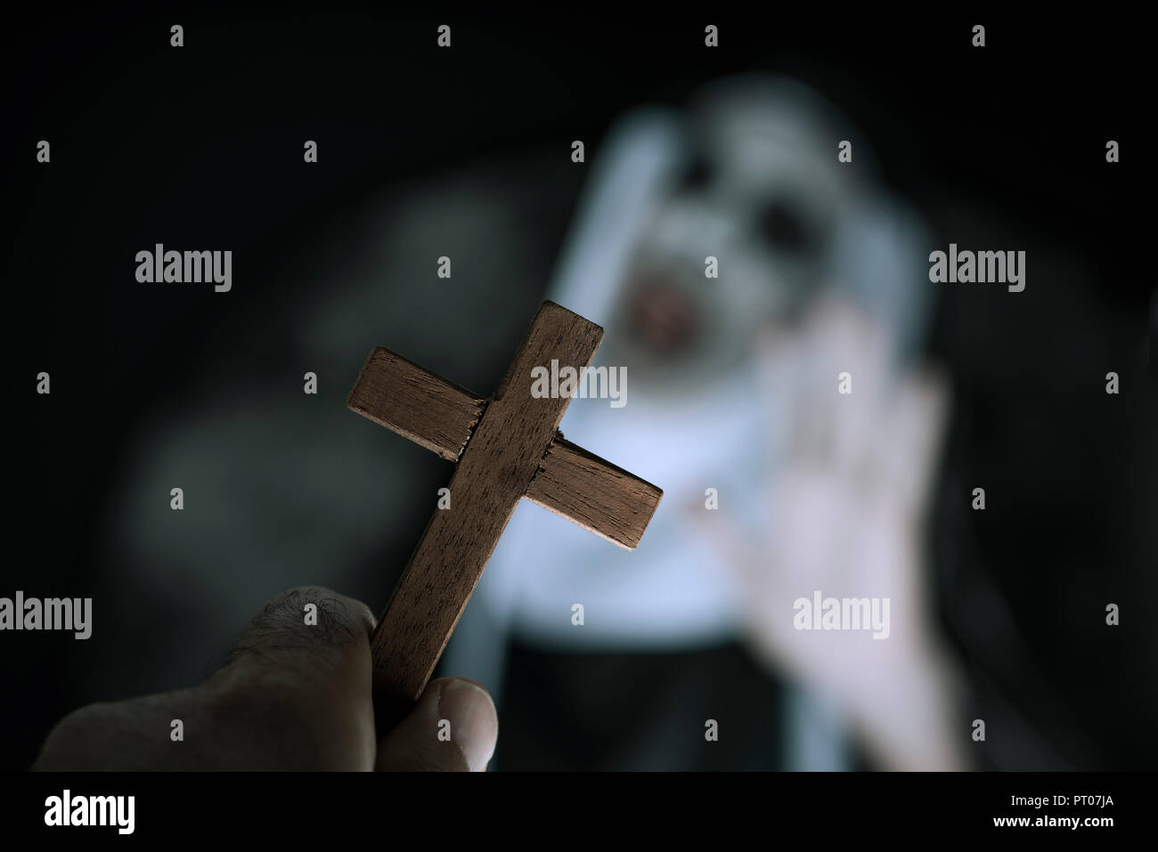 closeup a cross in the hand of a man and a frightening evil nun, wearing a typical black and white habit, screaming - Stock Image