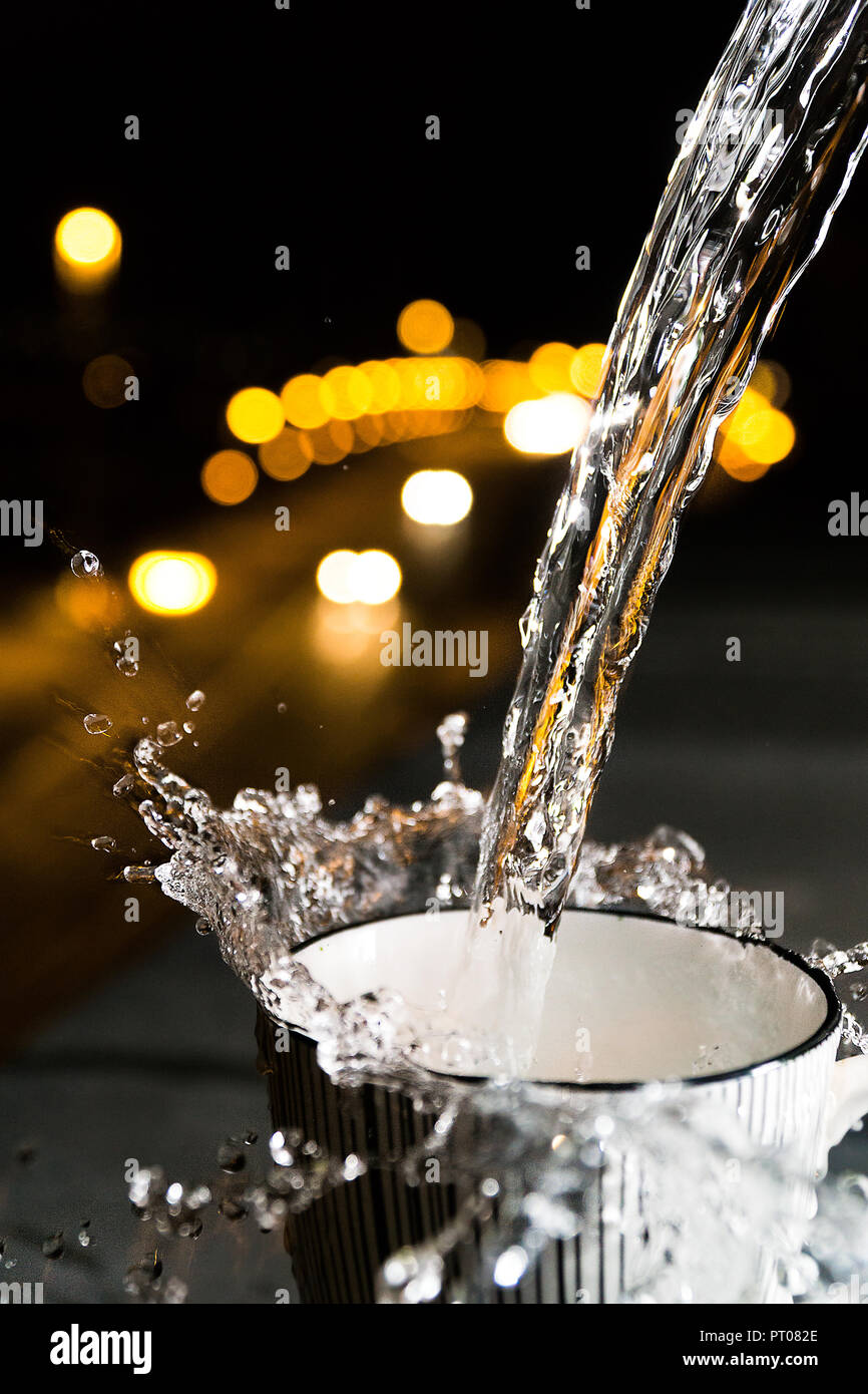 Male hand hols a cup with Splashing water and traffic bokeh lights in the background - Stock Image