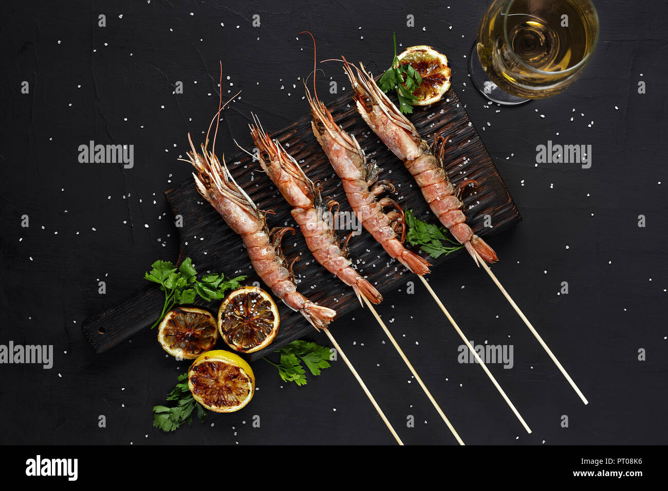 Grilled shrimp skewers. Seafood, shellfish. Shrimps Prawns skewers with herbs, garlic and lemon on black stone background, copy space. Barbecue shrimp Stock Photo