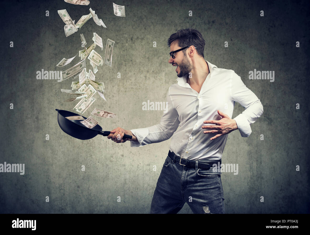 content suoper excited man with frying pan full of dollar bills on gray background - Stock Image