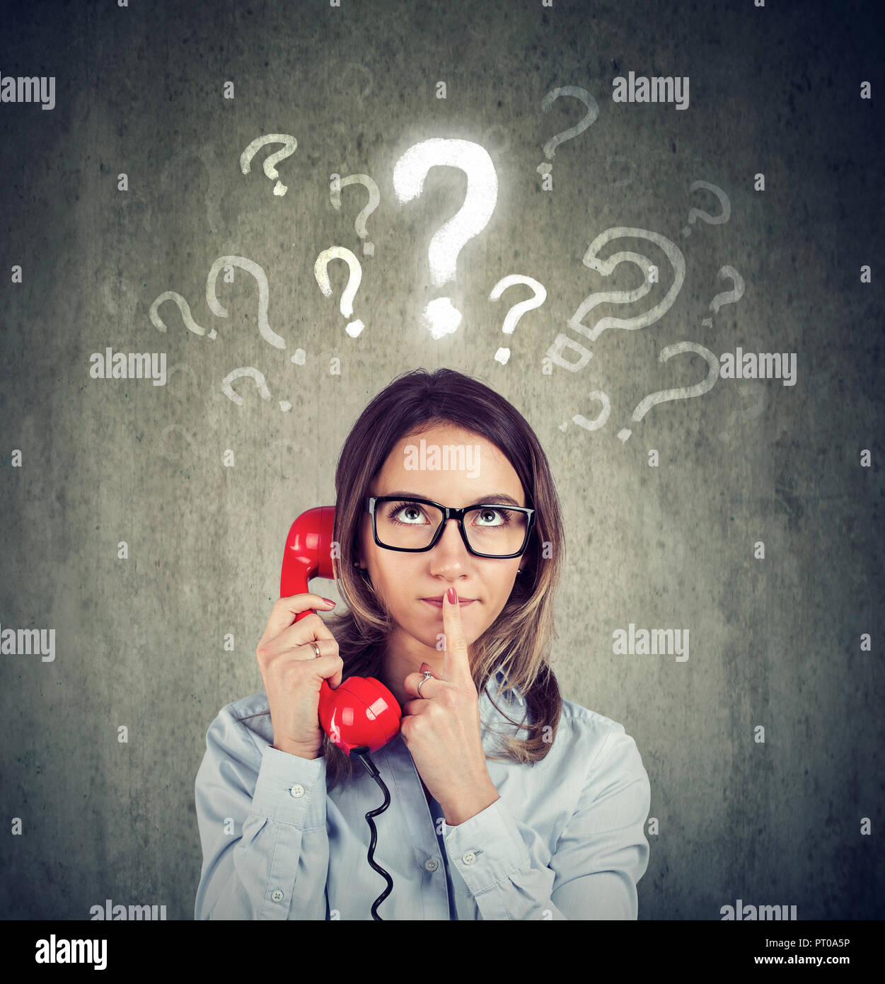 Misunderstanding and distant call. Confused worried woman talking on a phone has many questions isolated on gray background. - Stock Image