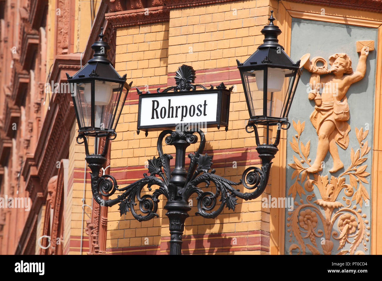 Old sign 'Rohrpost' with old street lamp at the former Postfuhramt in Oranienburger Straße, Berlin, Germany, Europe - Stock Image