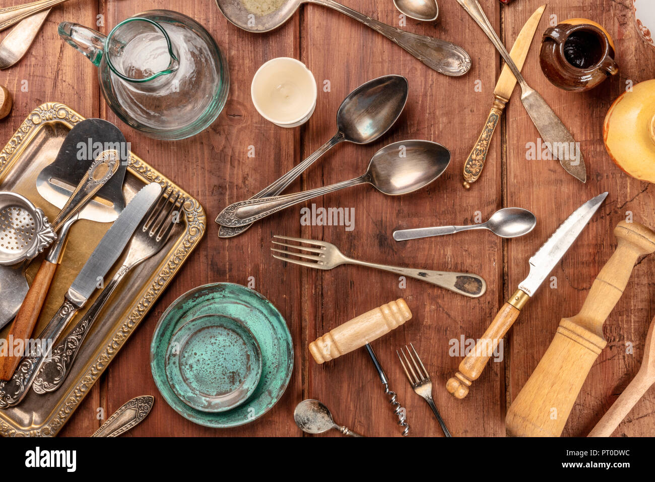 An overhead photo of many vintage kitchen objects and cutlery from an old restaurant, flea market stuff on a wooden background - Stock Image