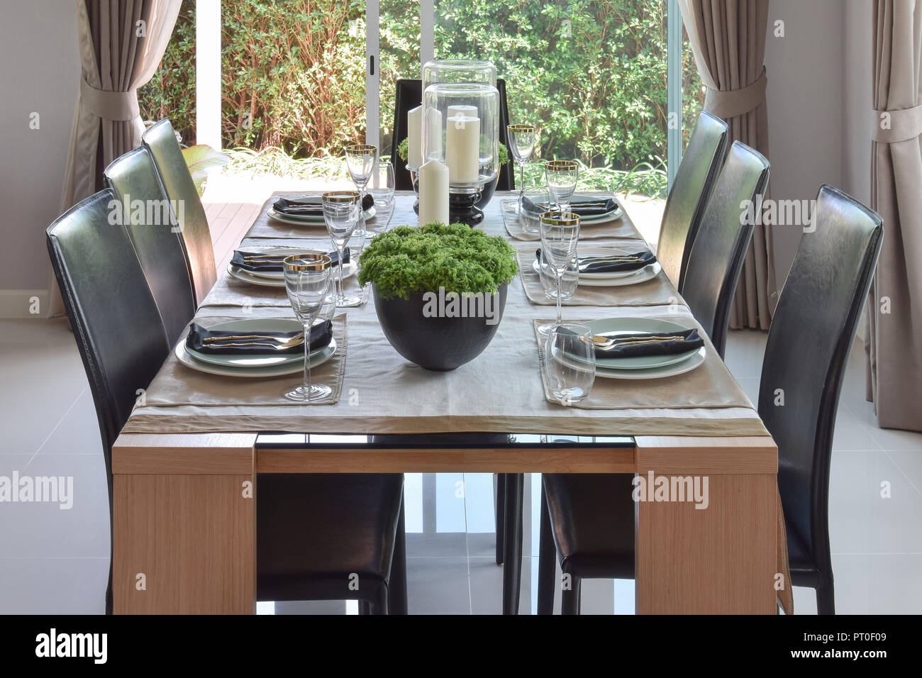 Dining Wooden Table And Comfortable Chairs In Modern Home With Elegant Table Setting Stock Photo Alamy