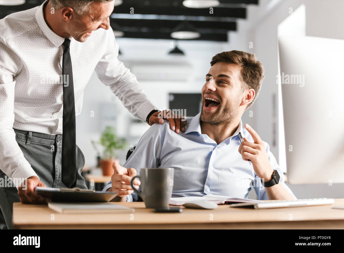 picture of excited happy emotional men colleagues in office working