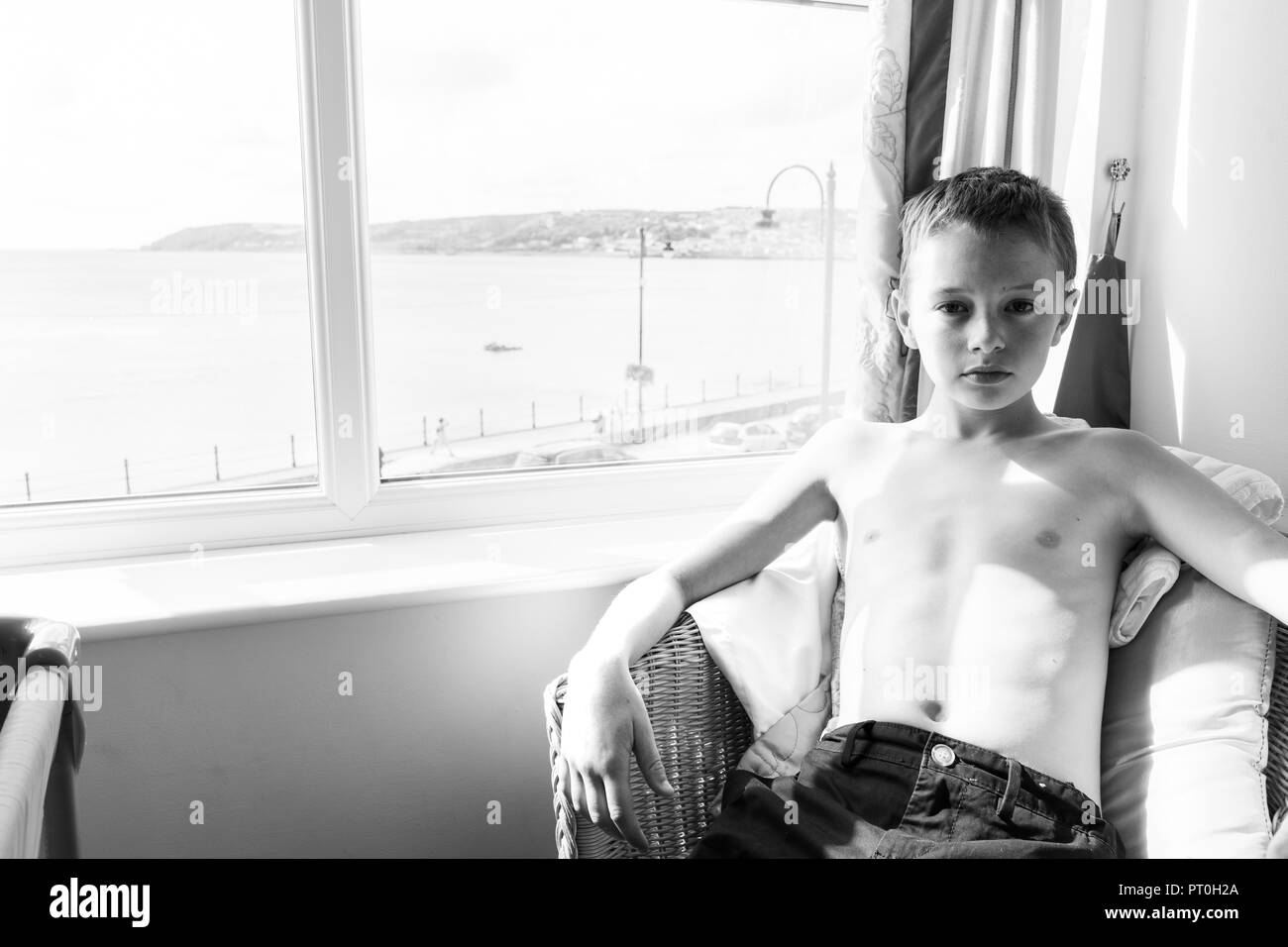 Little boy with autism/adhd sits in a chair in his hotel room with his shirt off, Asperger syndrome - Stock Image