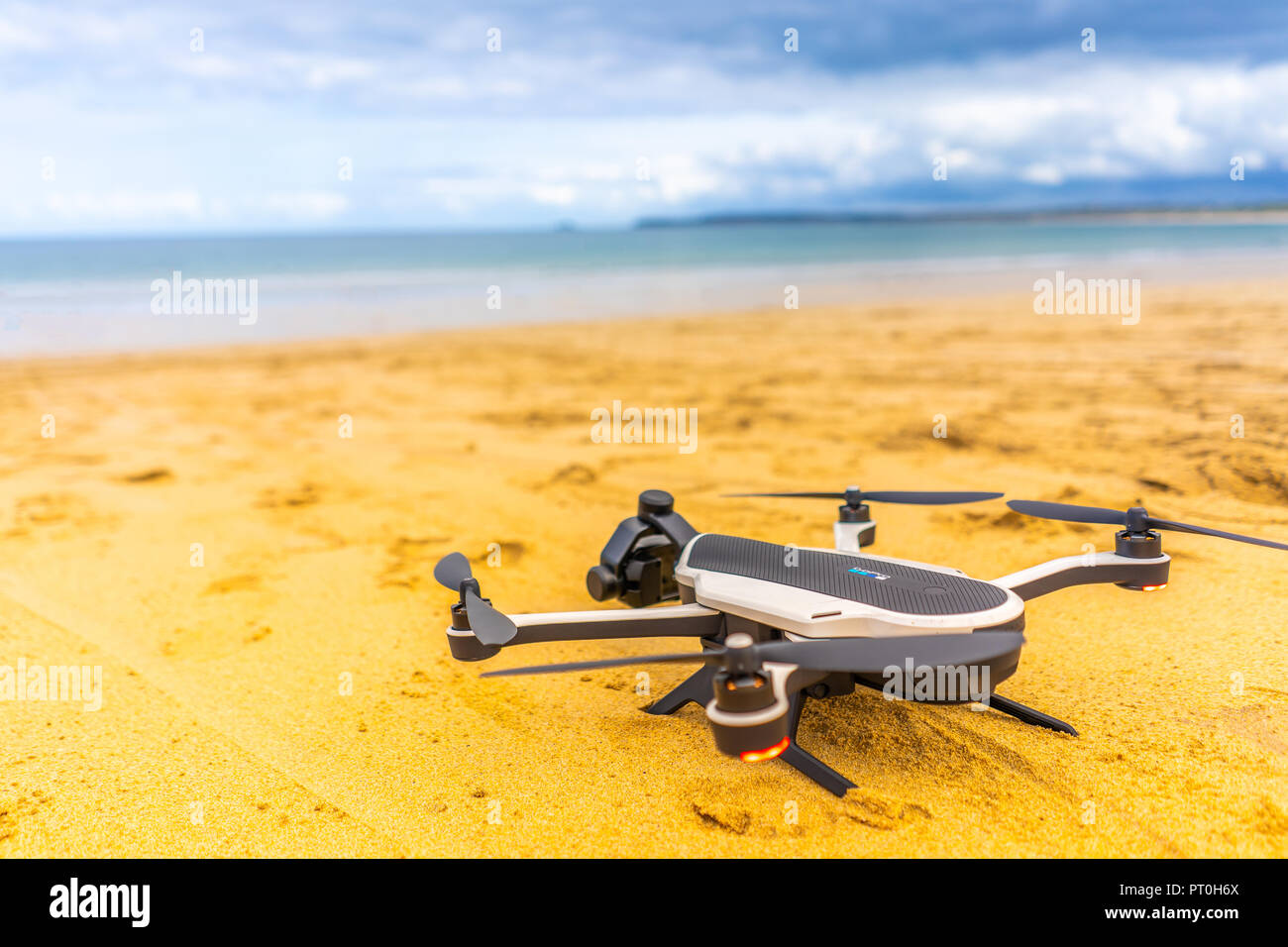A drone ready to take off from a beautiful sandy beach - Stock Image