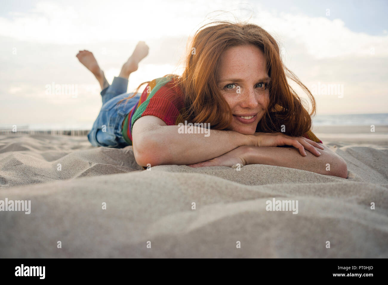 Redheaded woman lying in sand on the beach, smiling Stock Photo