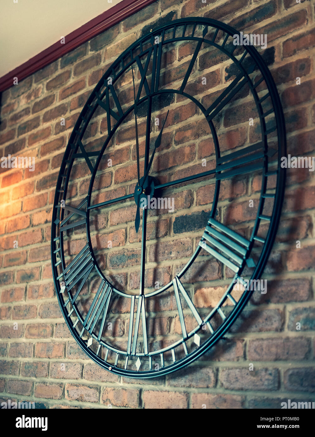 A Large Metal Clock On A Brick Wall In Daylight Stock Photo Alamy