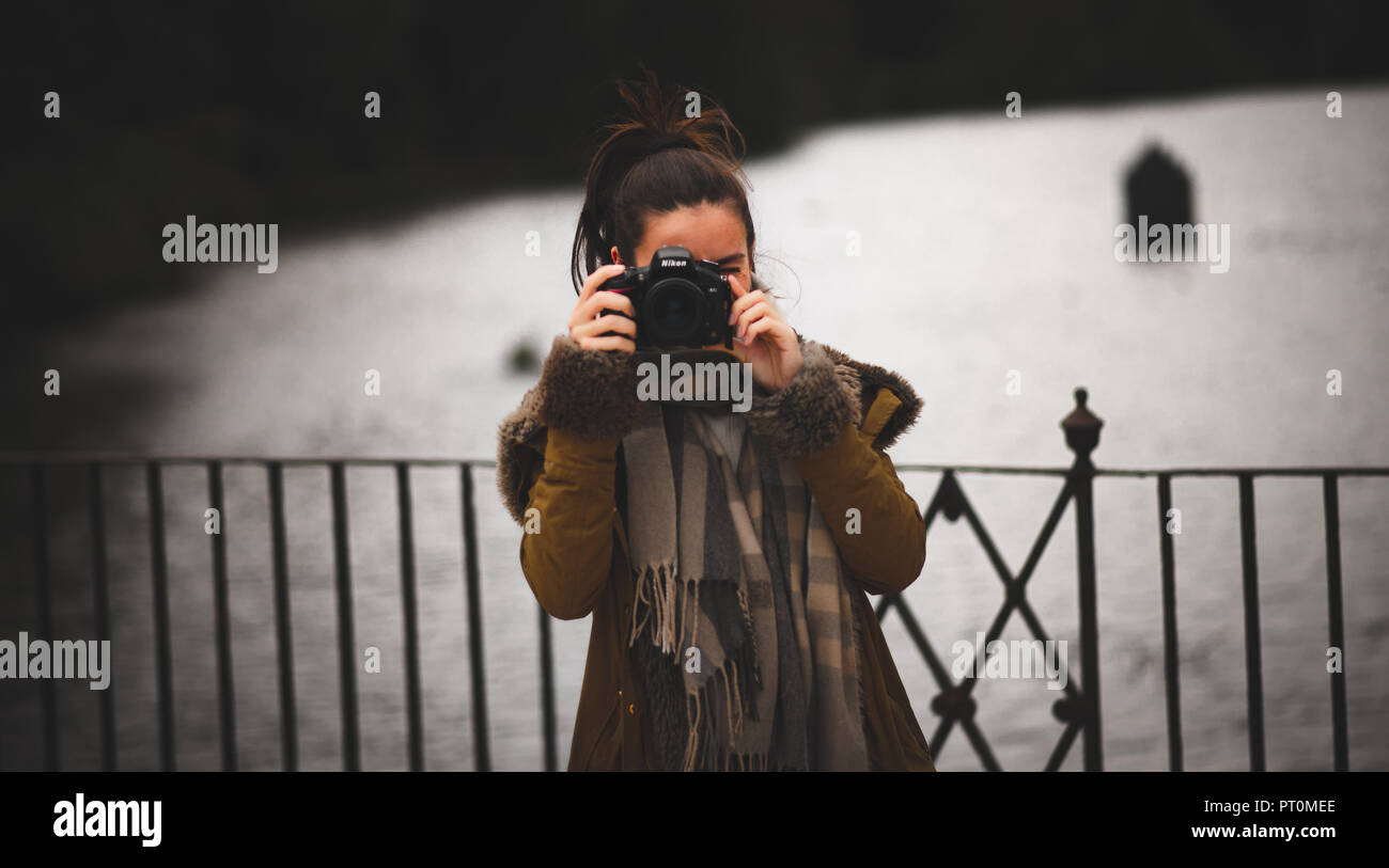 Young female photographer taking a photo of the camera - Stock Image