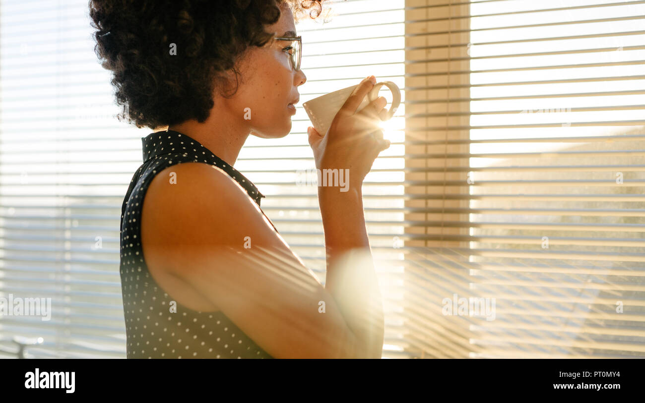 Young african businesswoman drinking coffee while standing by a window in office. Female looking outside and thinking about something while having cof - Stock Image