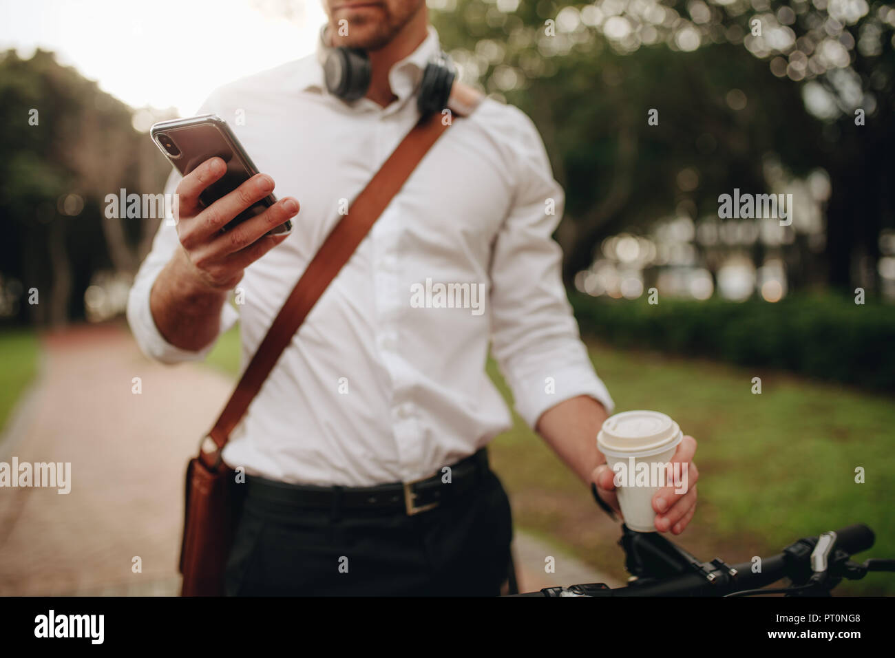 Man checking his mobile phone holding a disposable coffee cup while commuting to office. Businessman using mobile phone while walking to office. - Stock Image
