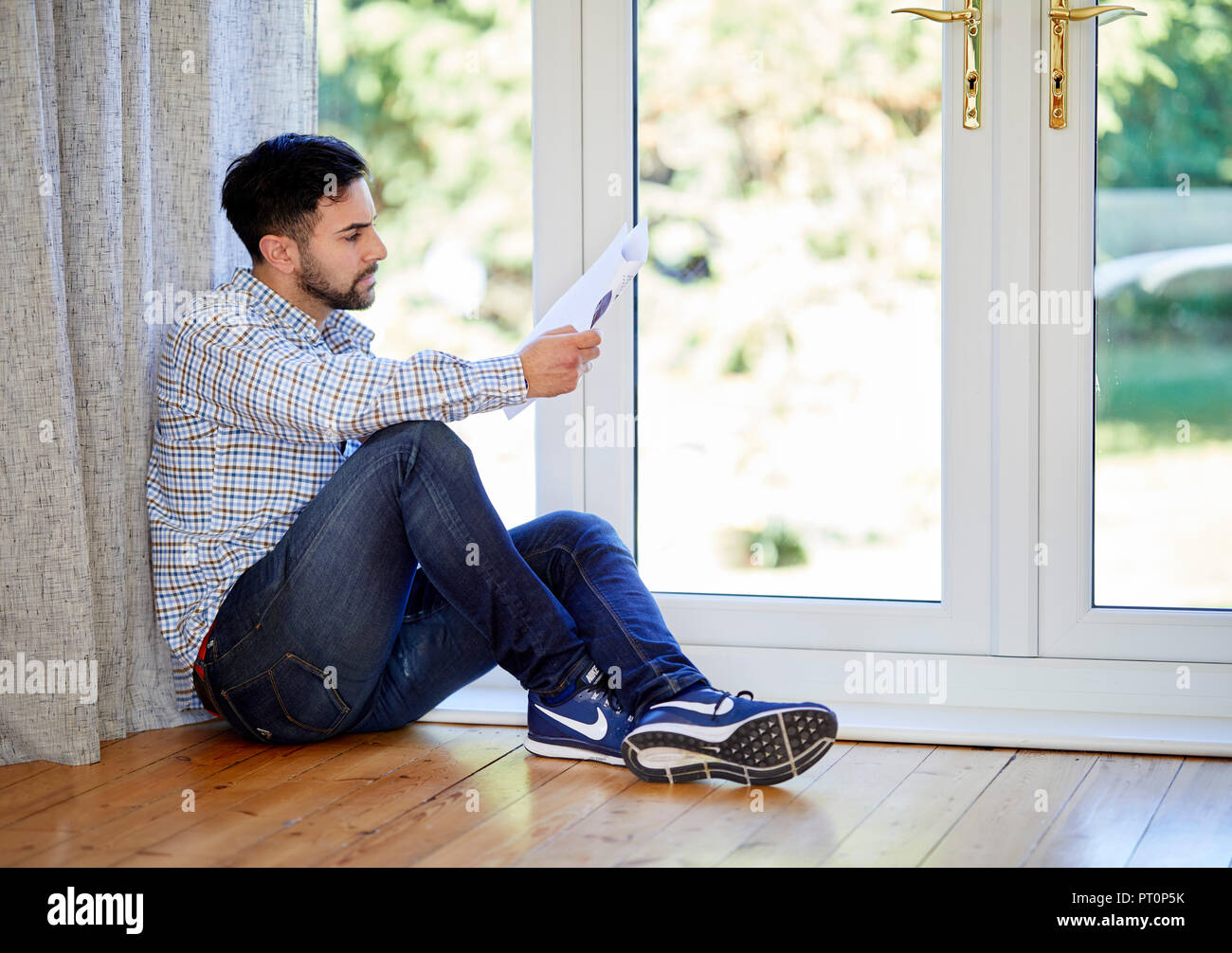 Man looking at his bank statement - Stock Image