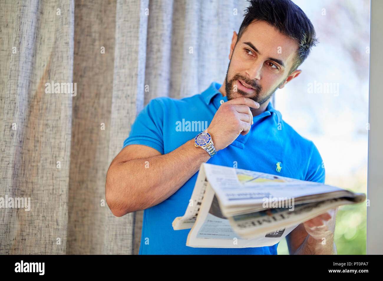 Man contemplating reading a paper - Stock Image