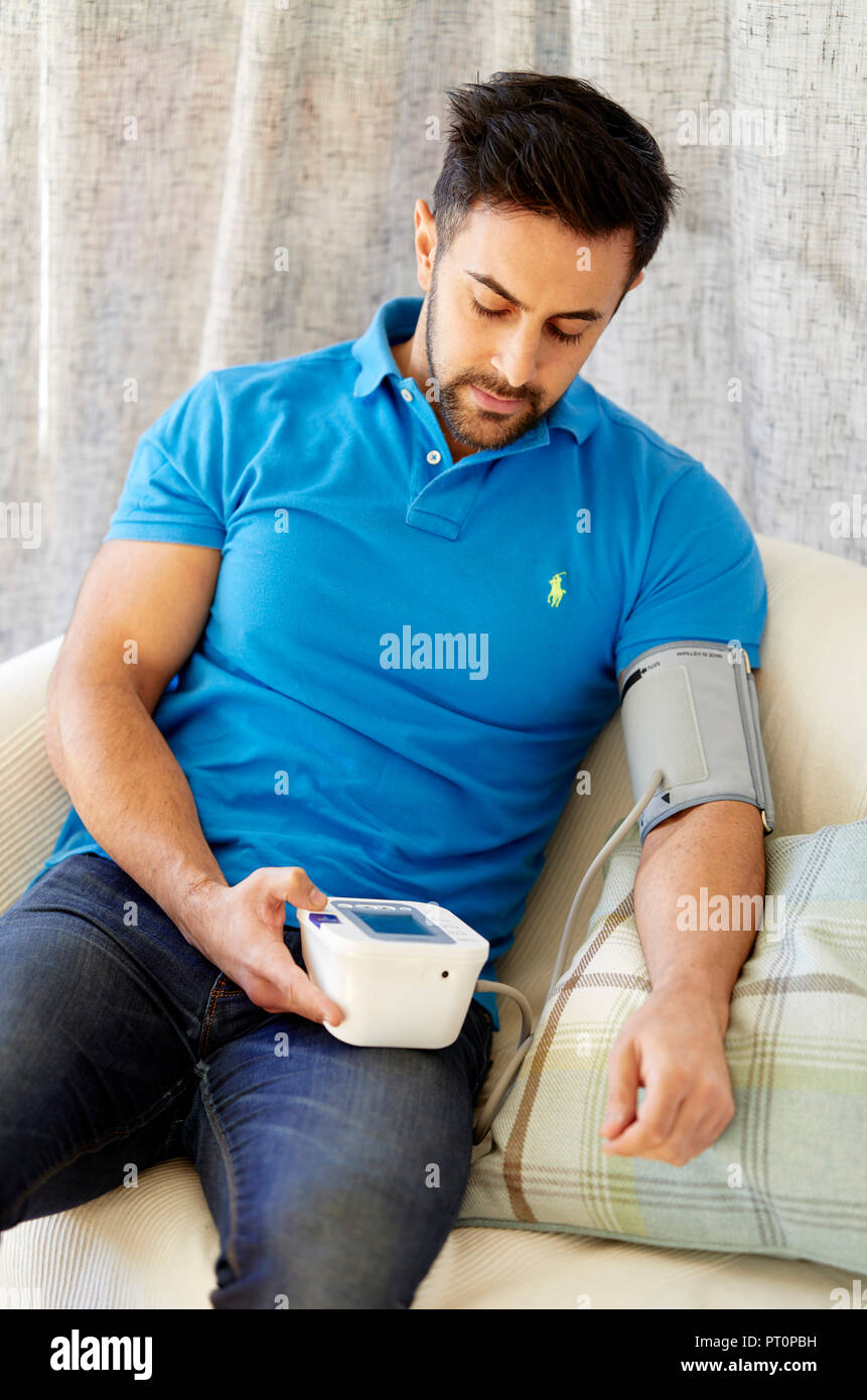 Man checking his blood pressure - Stock Image