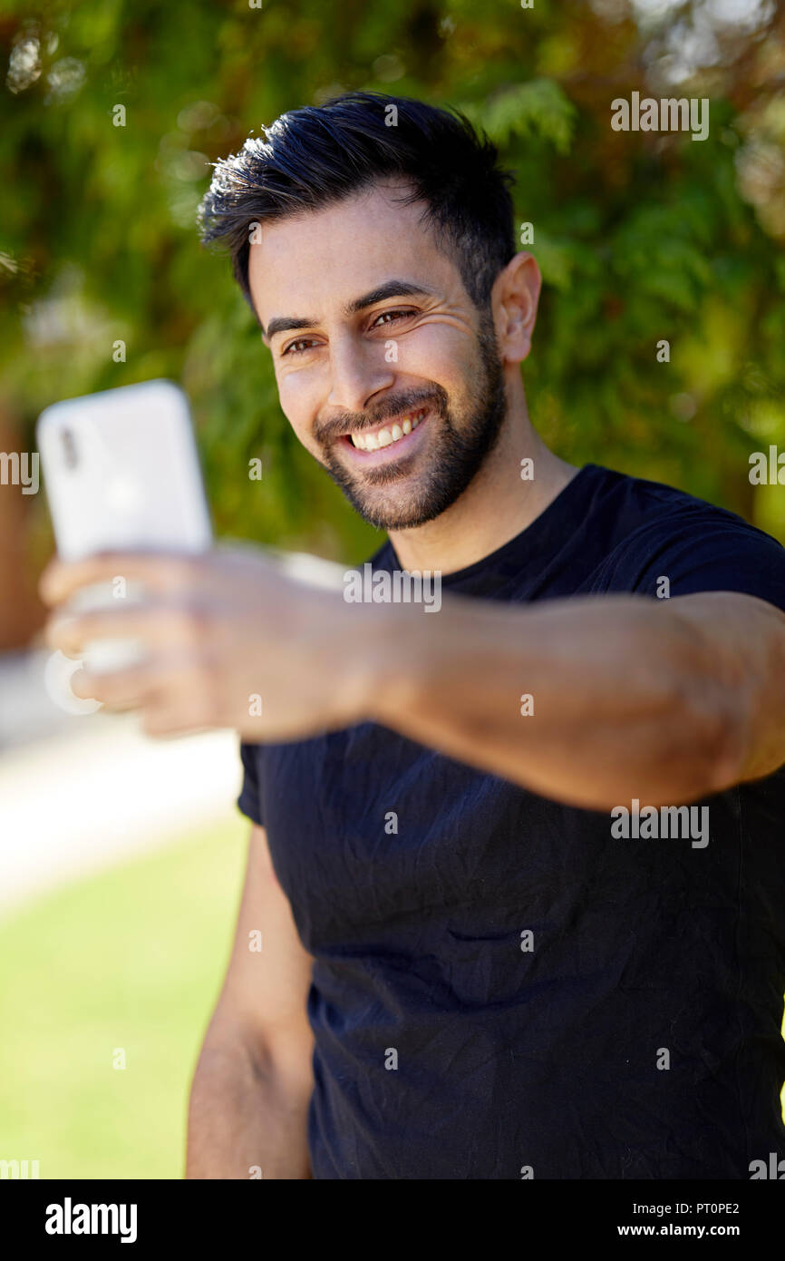 Male taking a selfie with his phone - Stock Image