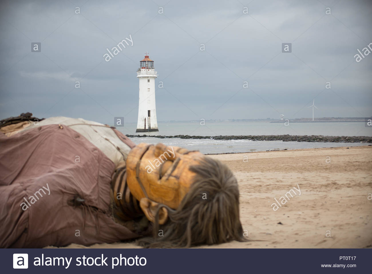 Royal De Luxe Giant asleep at New Brighton on the Wirral as part of Liverpool's Dream Giant Spectacular Stock Photo