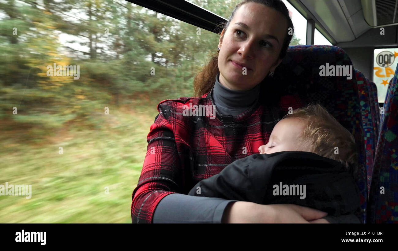 Mother holding her baby while commuting by bus. Casual shot of commuter single mother with her baby traveling by bus. - Stock Image
