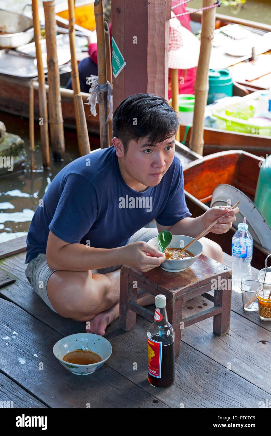 Young man eating soup at the Damnoen Saduak Floating Market, Thailand, SE Asia Stock Photo