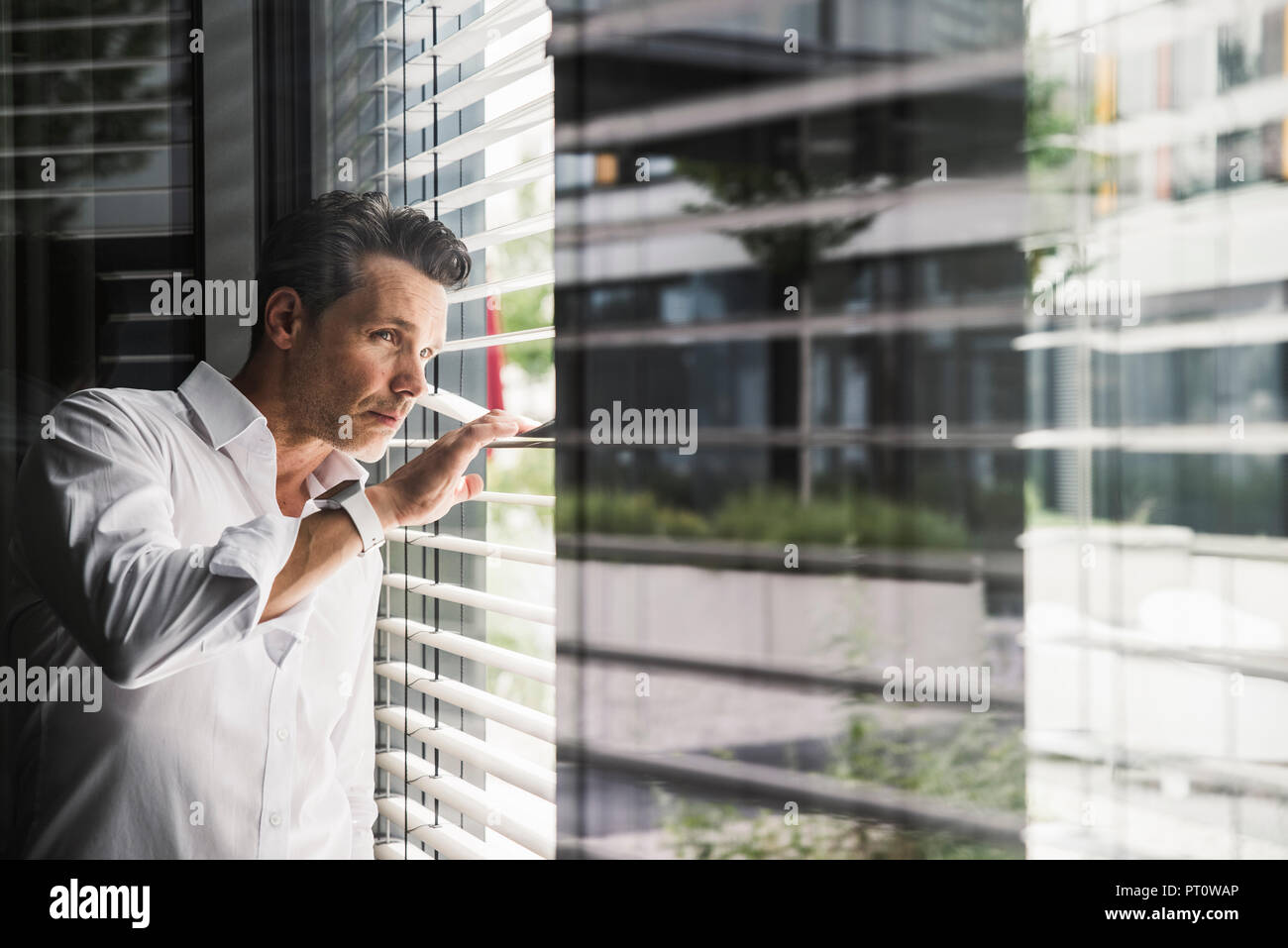 Businessman peeking through sunblinds at the window in office - Stock Image