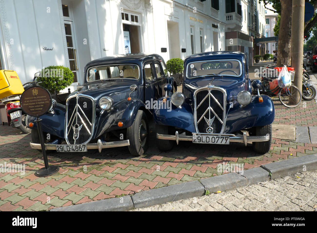 Hanoi Vietnam - Old style Citroen saloon cars outside the Hotel Metropole in the Old Quarter of Hanoi - Stock Image