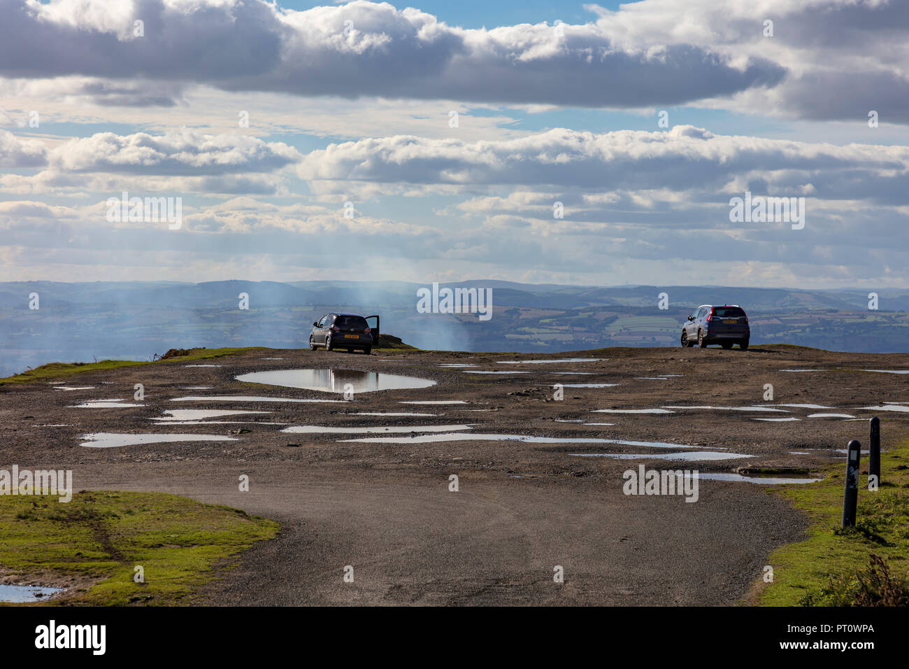 Cars parked on the old quarry workings at Titterstone Clee Hill, taking advantage of the long views towards ludlow, Shropshire, UK - Stock Image