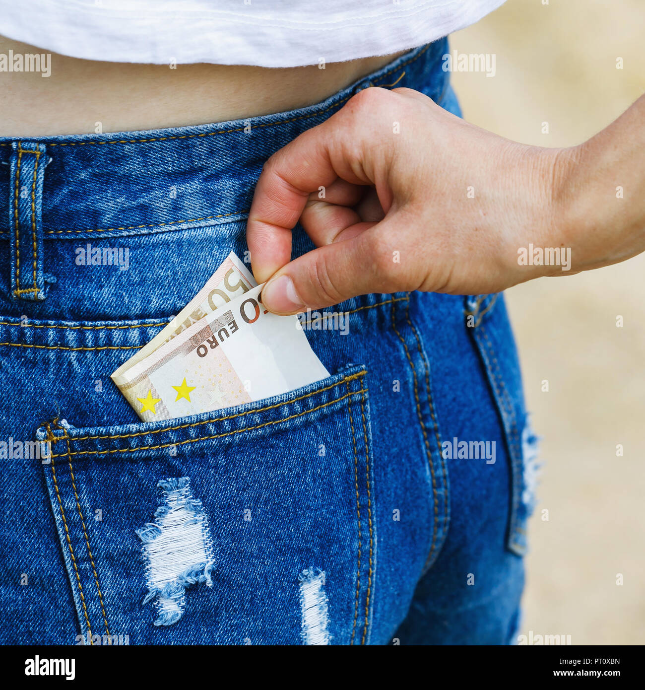 Theft of currency from pocket of jeans at not attentive tourists - Stock Image