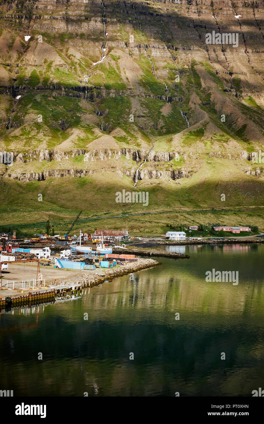 Old fishing trawlers and houses in the small port town of Seydisfjordur in the East Fjords of Iceland. - Stock Image