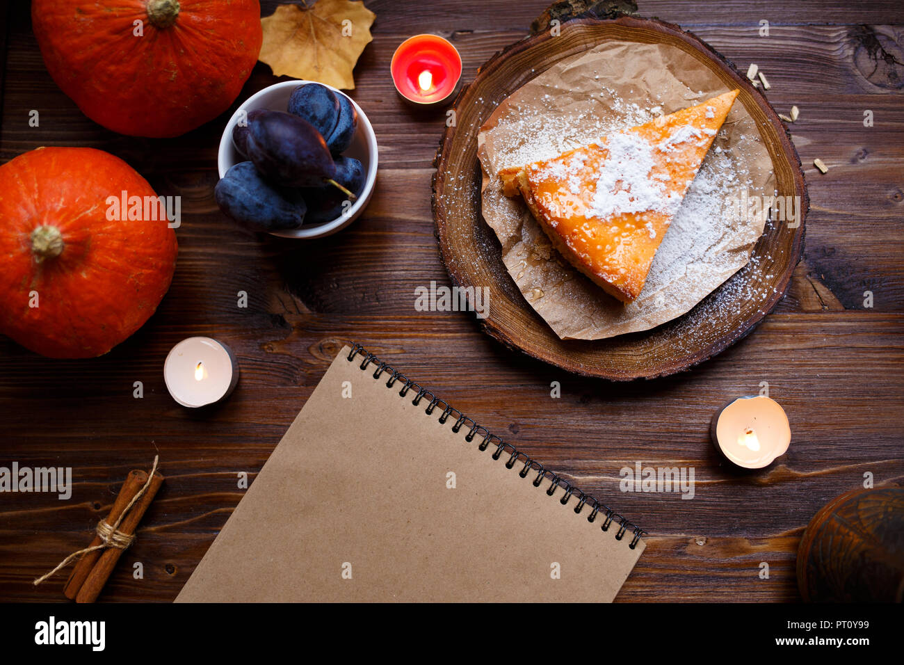 Notebook, pumpkin cheesecake, cooked at home, pumpkin, foliage, table lamp, vanilla on a wooden dark table. Autumn and winter cozy concept. - Stock Image