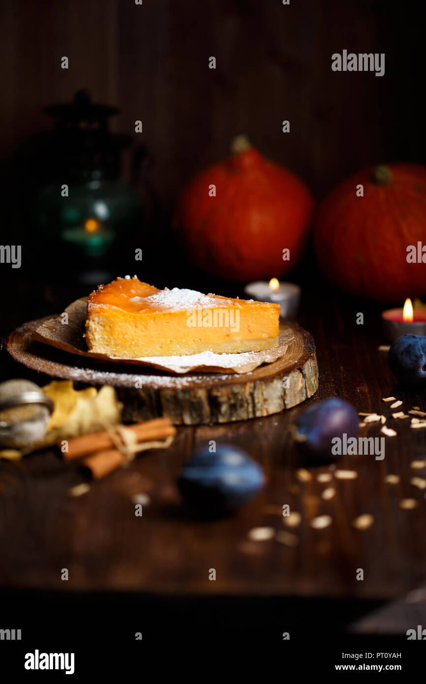 Piece of pumpkin cheesecake with powdered sugar, pumpkins, table lamp on a dark wooden background - Stock Image