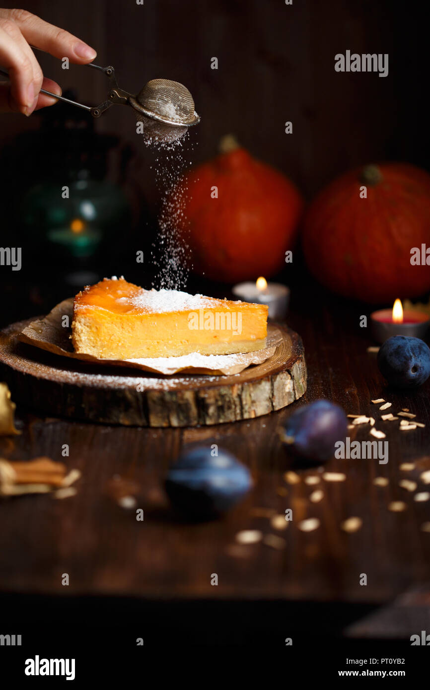 Female hand sprinkles powdered sugar on pumpkin cheesecake. Pumpkins, table lamp, foliage, vanilla on a wooden dark background. - Stock Image